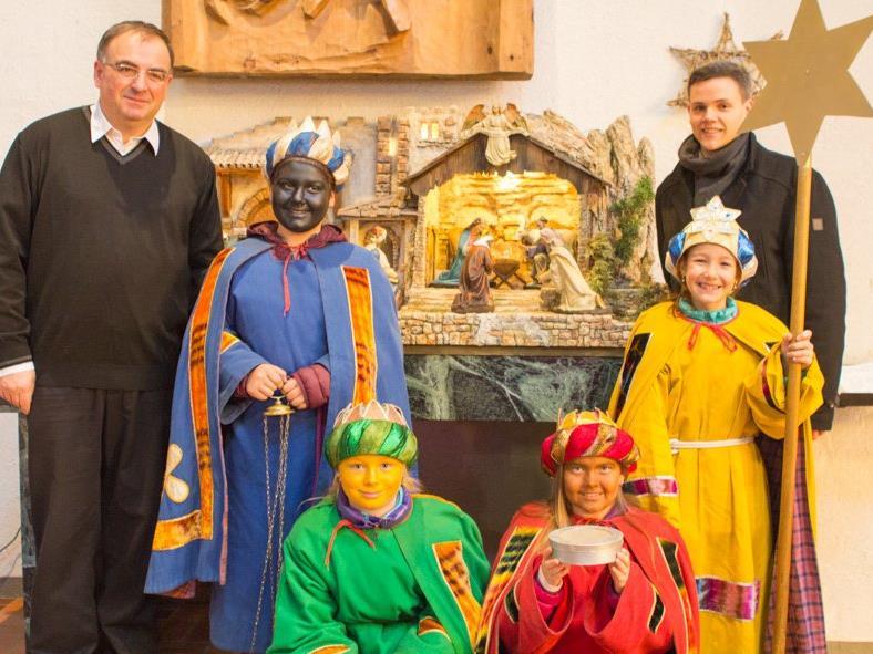 Pfarrer Tinkhauser freut sich mit den Kindern und den Organisatoren Petra Bitschnau und Thomas Schuler über das tolle Sammelergebnis.