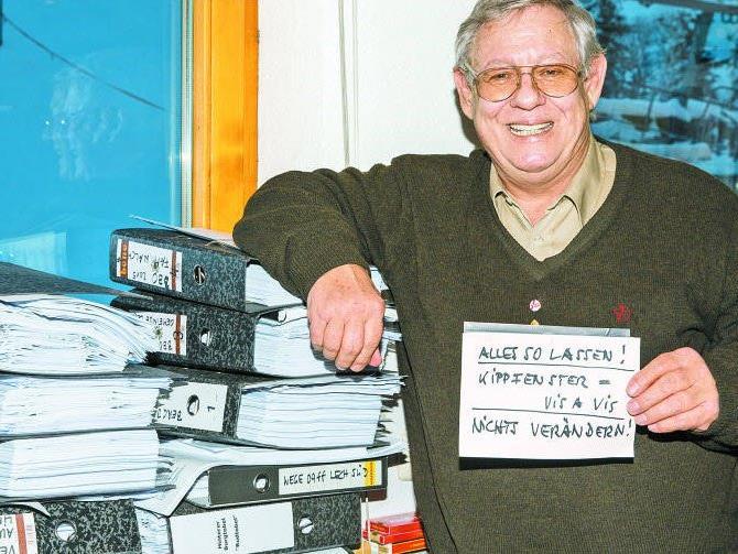 """Seilbahn-Urgestein Michael Manhart vor einem Stapel Akten. Nur er selbst hat den Überblick in seinem """"System""""."""