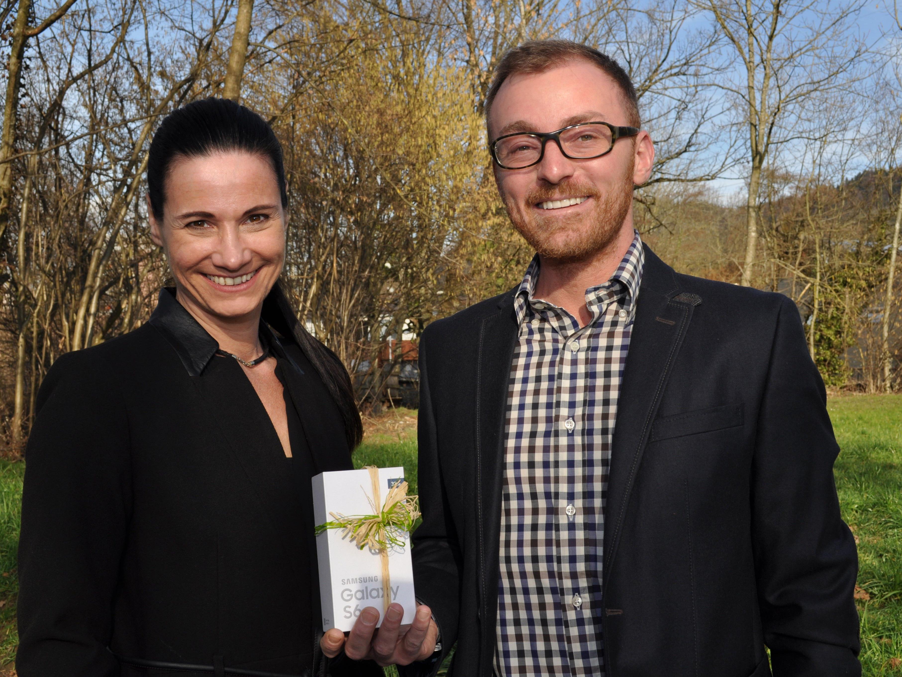 Barbara Stanzel, Leiterin der Sparkassenfiliale Leiblachtal, bei der Übergabe eines NFC-fähigen Smartphones an Herrn Wolfgang Vögel.