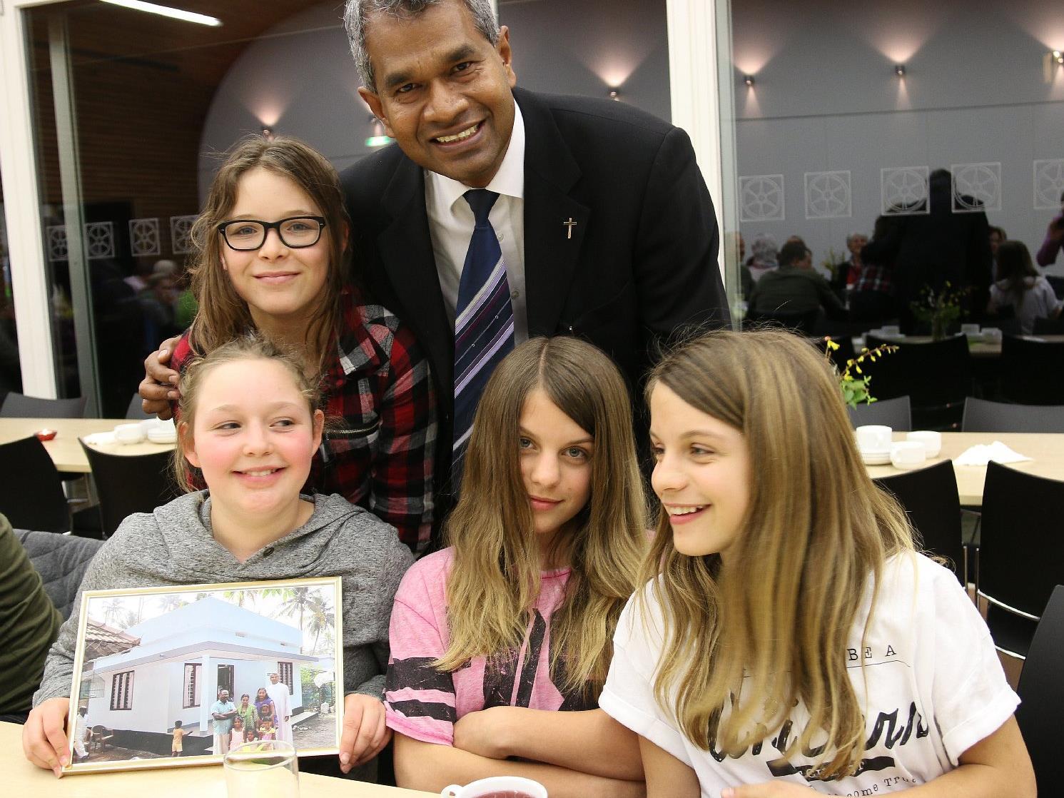 """Cora, Norah, Nina und Leonie mit einem Foto """"ihres"""" Hauses."""