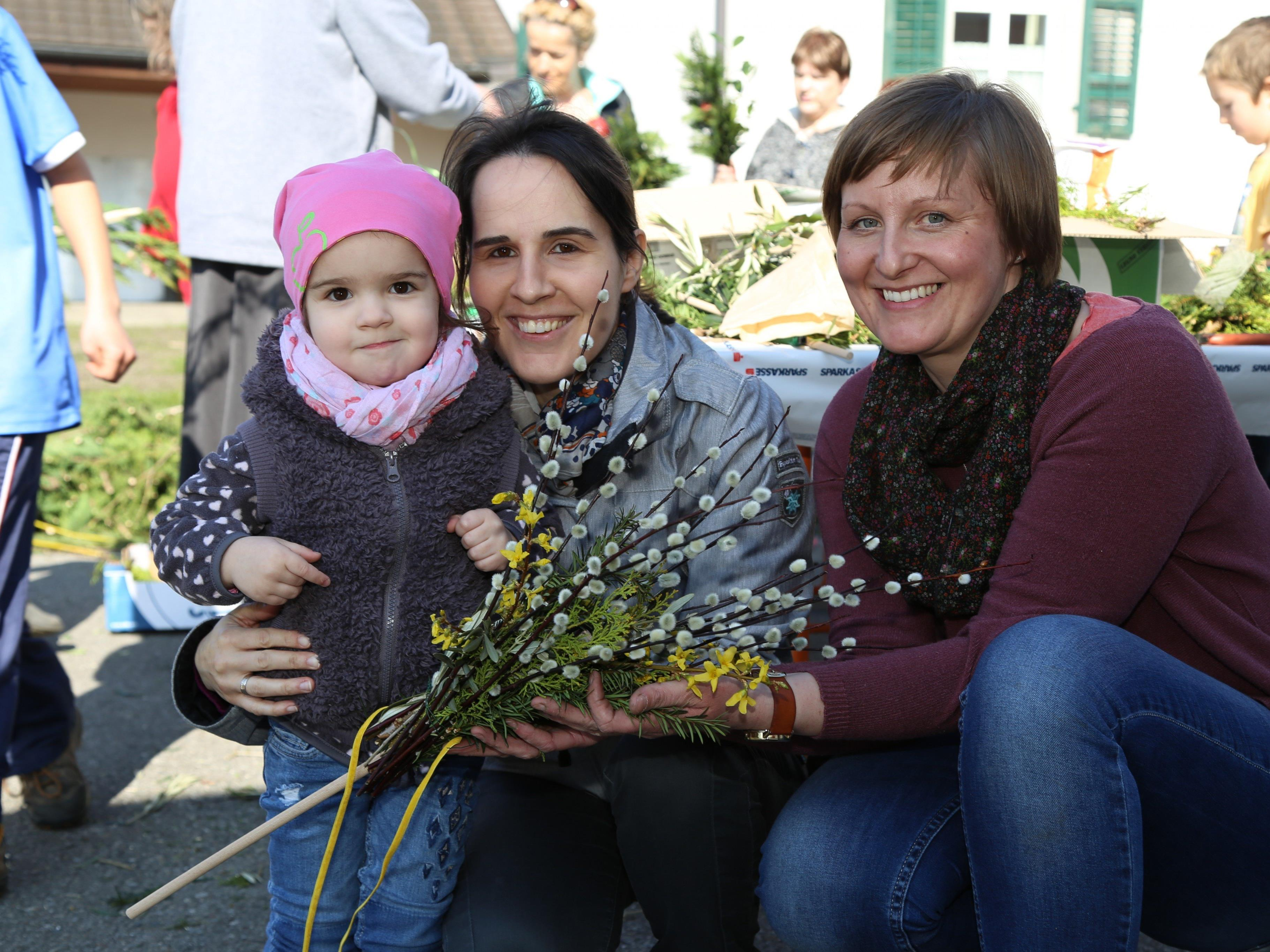 Yvonne Lins (r.) half den Kindern schöne Palmbuschen zu binden.