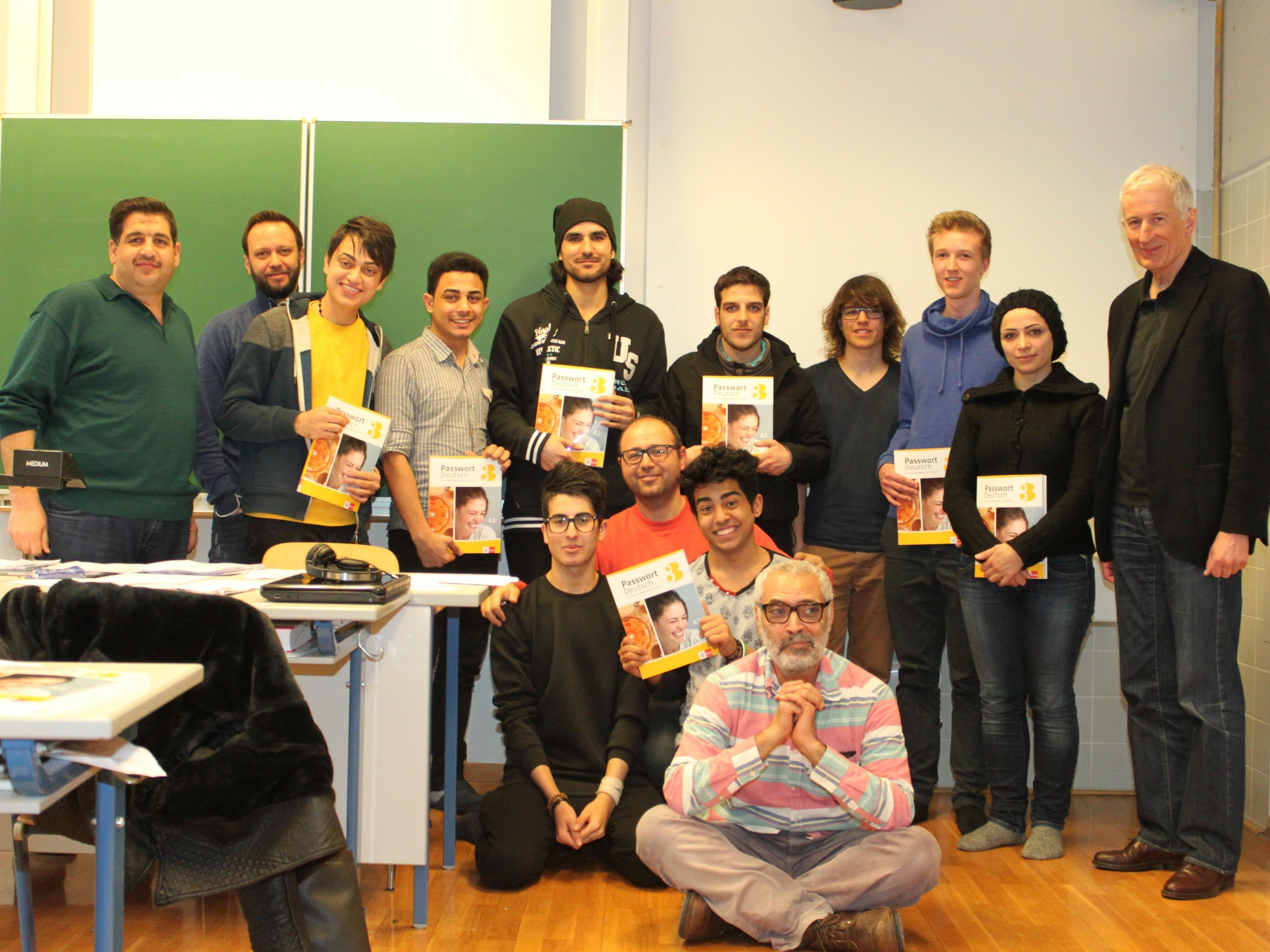 Bürgermeister Mag. Wilfried Berchtold (r.) überreichte Flüchtlingen sowie Professor Aly El Ghoubashy (sitzend vorne) aus Spenden finanzierte Schulbücher.