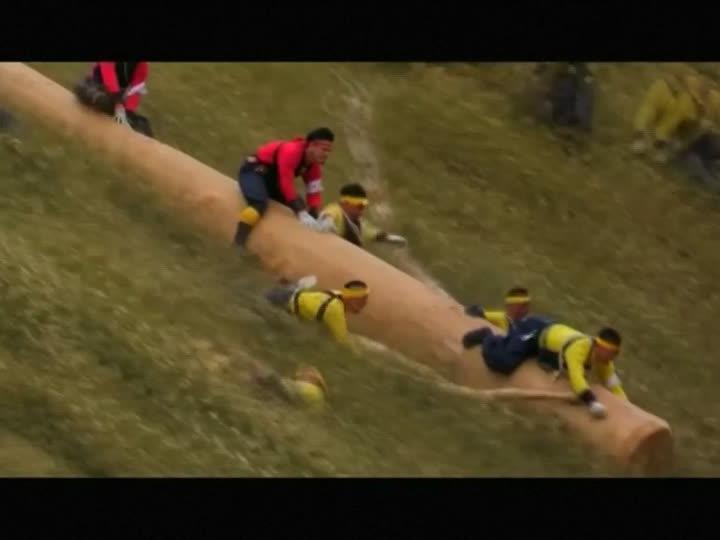Auf Baumstämmen stürzen sich die Männer einen Hang hinunter.