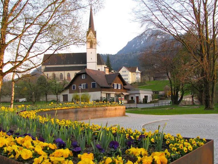 Einer von vielen genannten Gründen: Die vielen Blumen wie hier im Gemeindepark mit Blick auf die gotische Pfarrkirche.