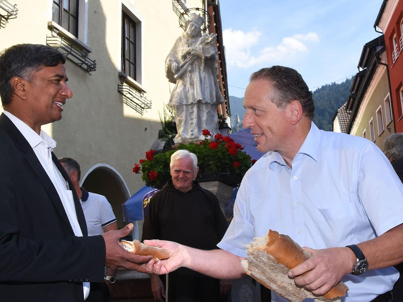 Der Arbeiterkammerpräsident reicht dem Bludenzer Kaplan ein Stück Brot.