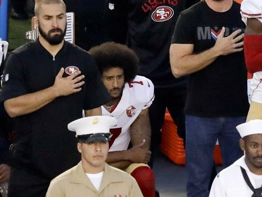 Colin Kaepernick (mitte) kniet während der US-Hymne vor dem Pre-Season-Spiel der San Francisco 49ers gegen die San Diego Chargers.