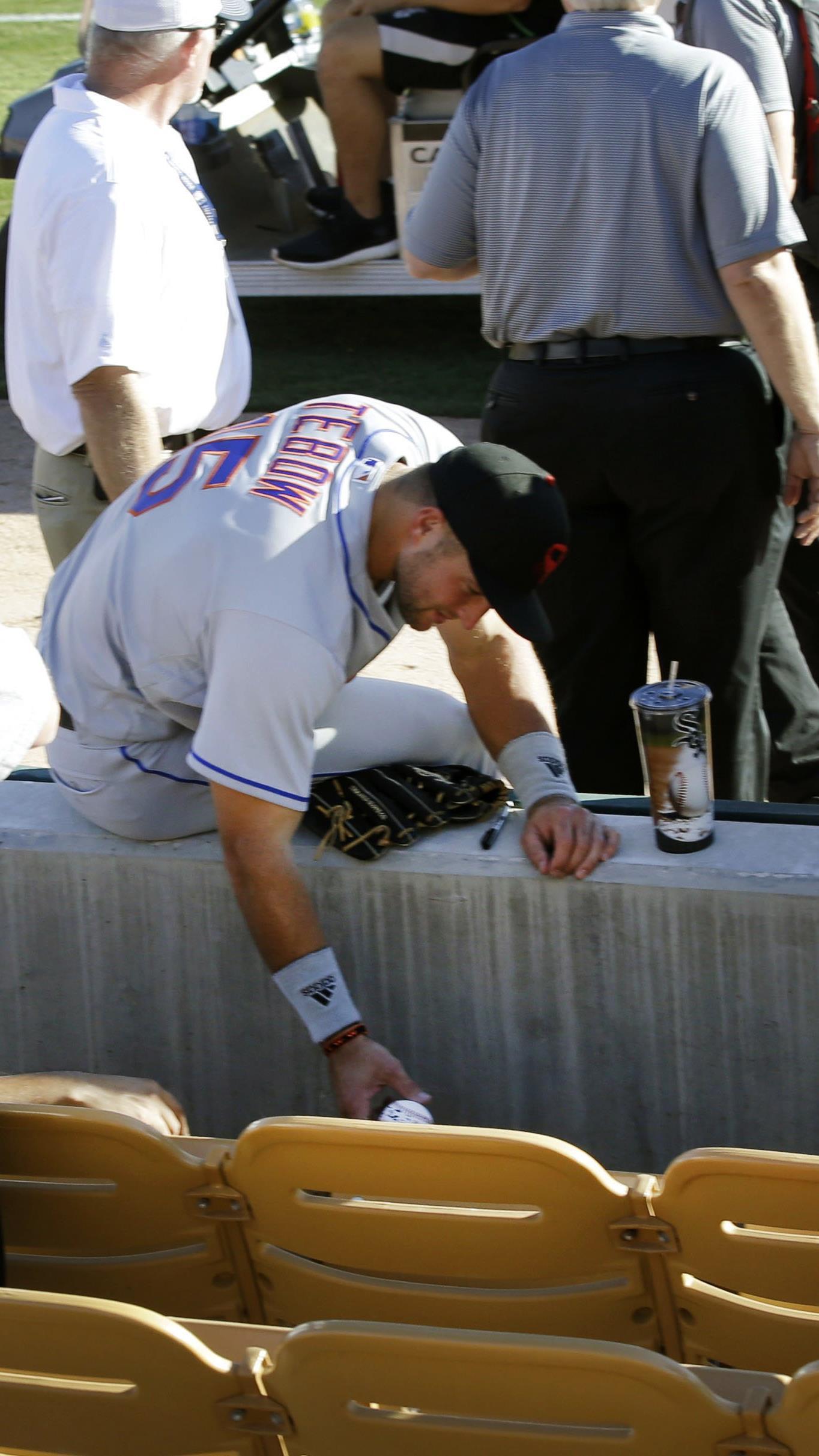 US-Sportler Tim Tebow (Mitte) kümmerte sich bei einem Baseball-Spiel um einen zusammengebrochenen Fan.
