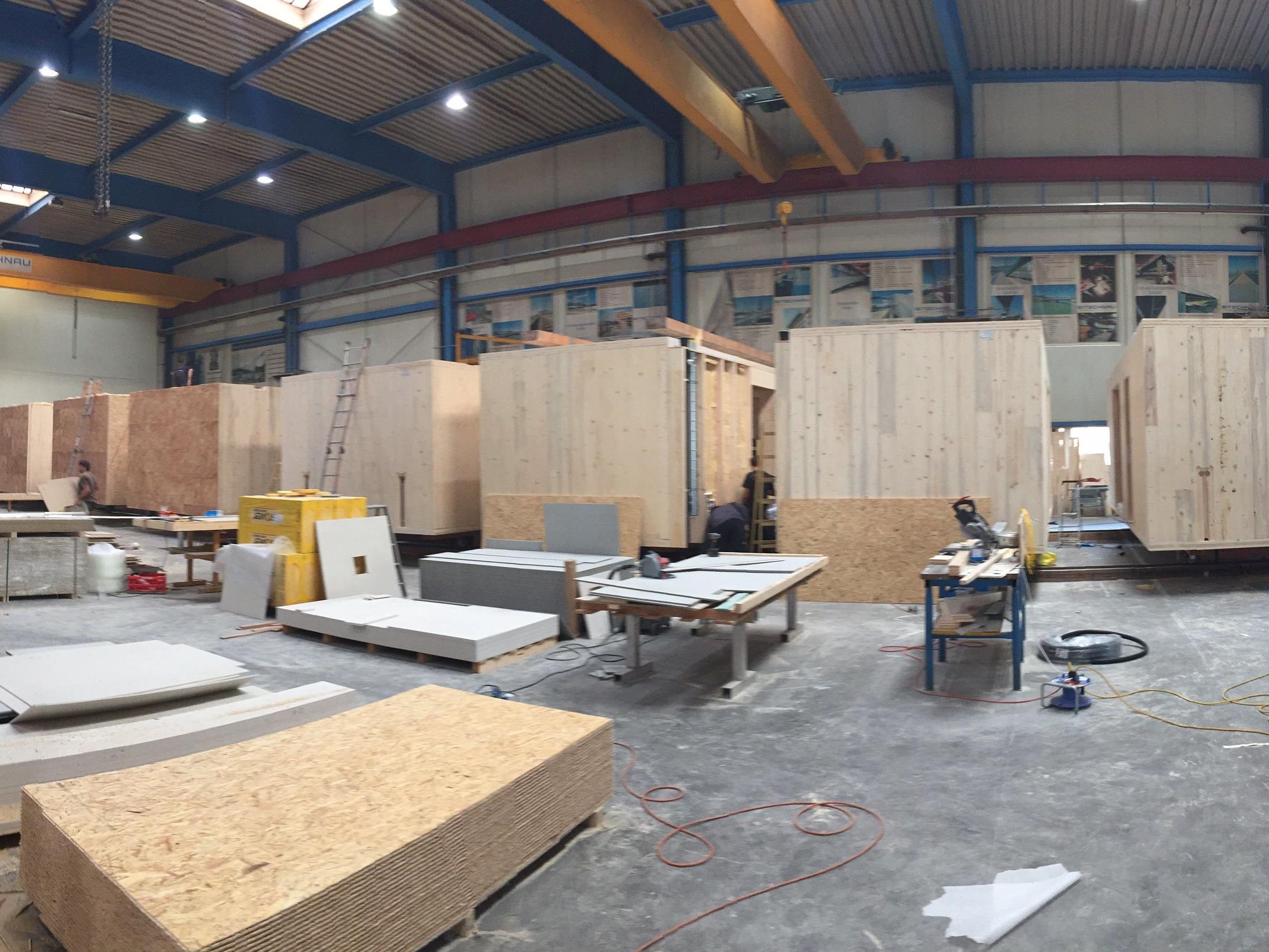 Von rechts nach links wandern die einzelnen Wohnmodule: vom reinen Holzkörper bis zum fertig ausgestatteten Wohnmodul.