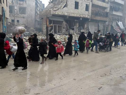 Die Menschen flüchten aus zerbombten Bezirken