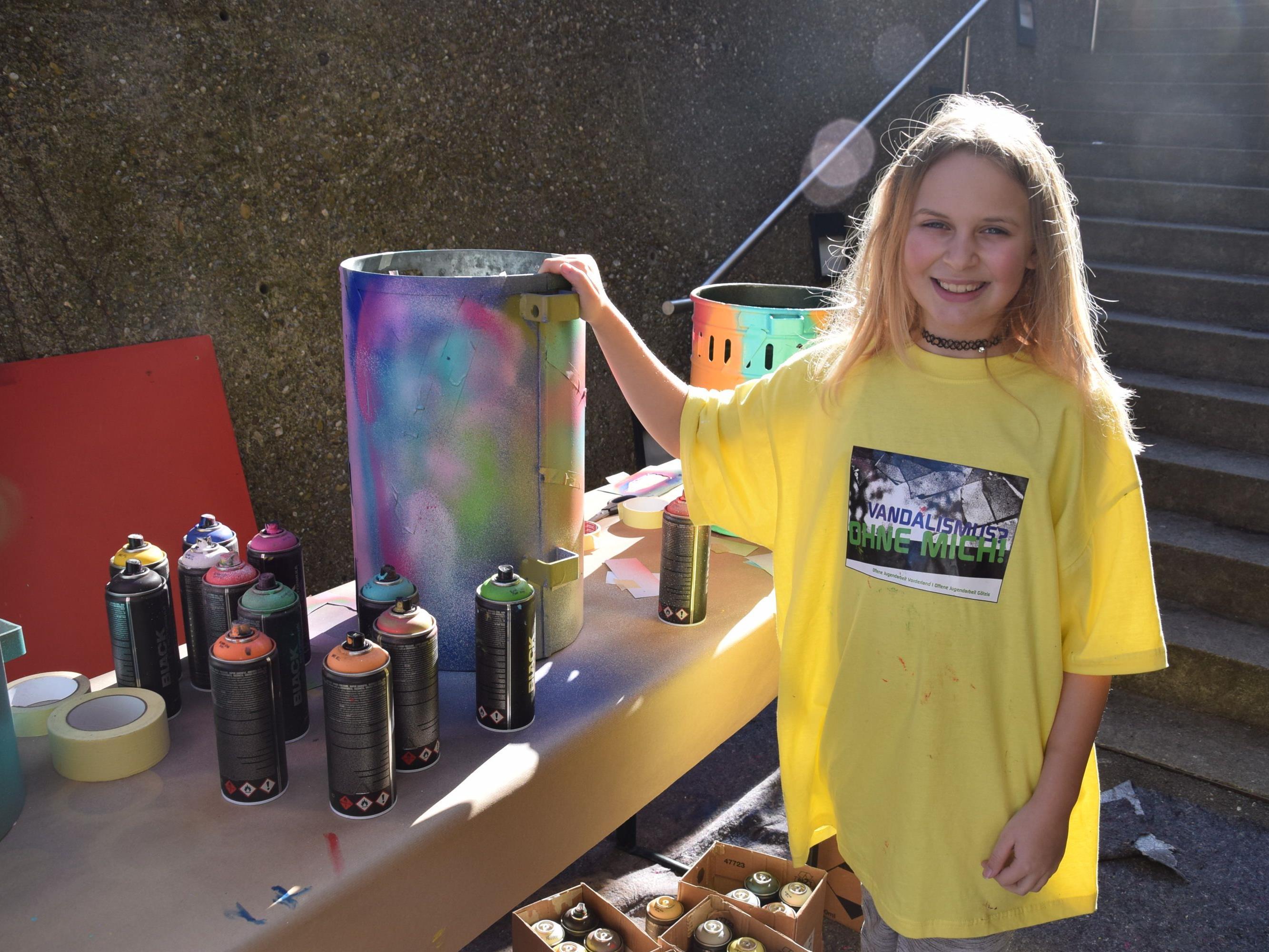 Anna-Lena gestaltete die Mülleimer für die Gemeinde mit bunten Farben