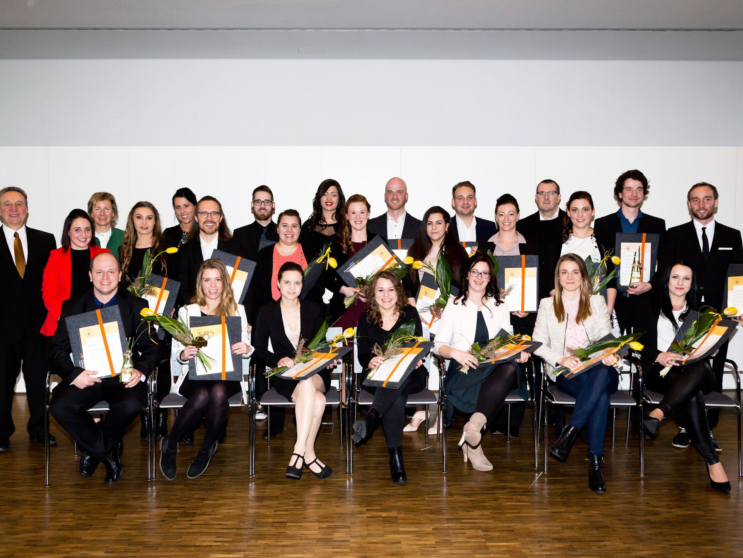 23 erleichterte, strahlende Absolventinnen und Absolventen bei ihrer Diplomfeier.
