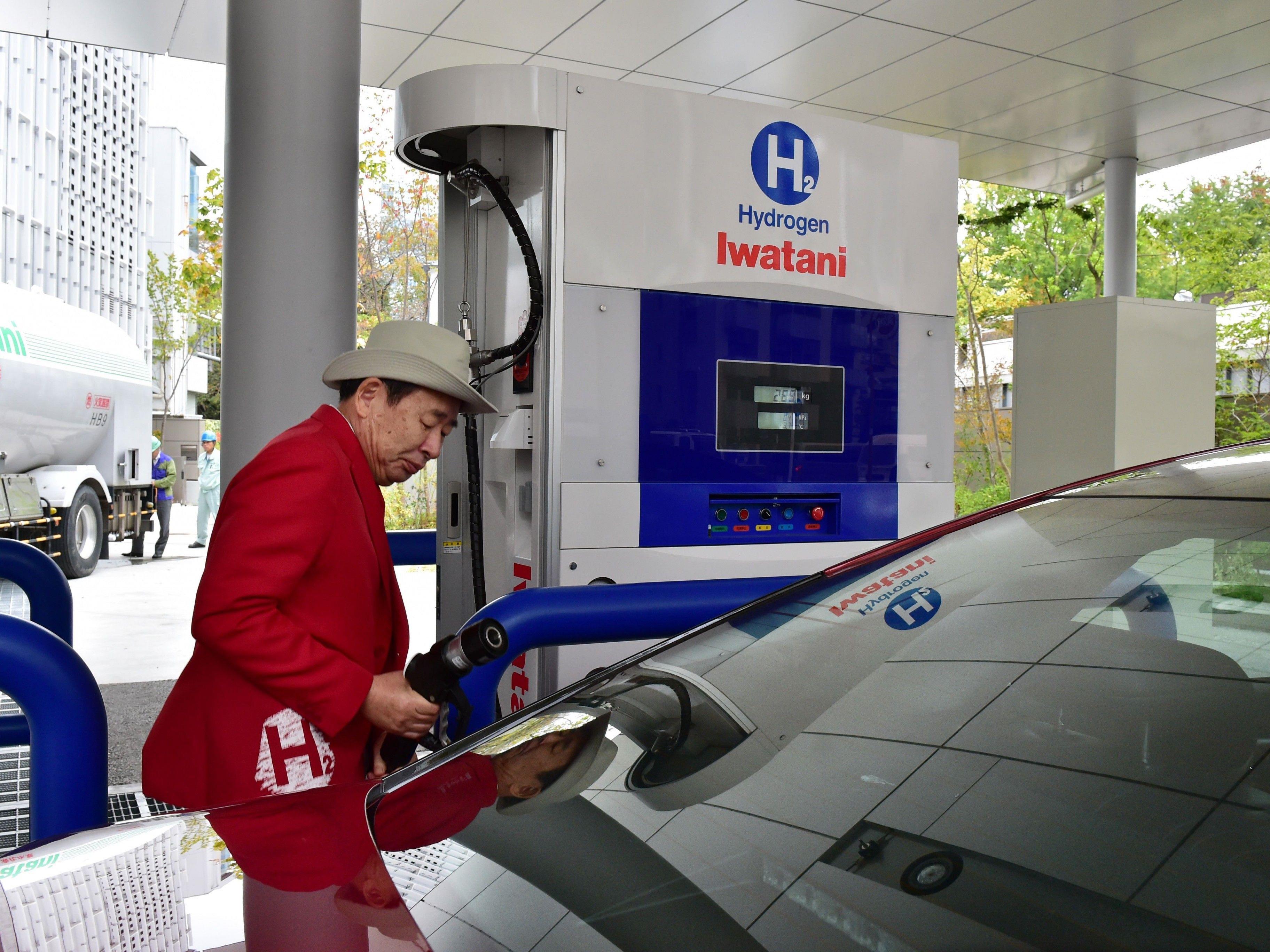 Japanischer Senior beim Befüllen eines Autos.