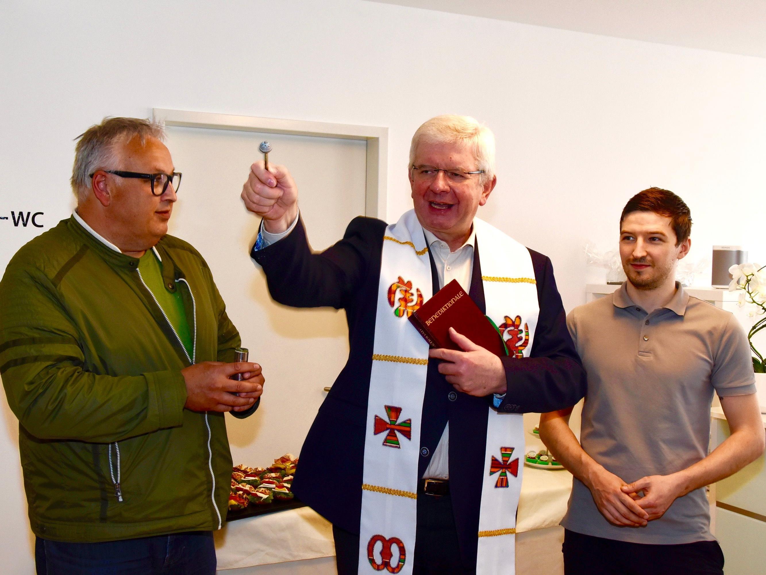 """Stadtpfarrer Pater Adrian Buchtzik bei der Segnung; links von ihm """"Ministrant"""" Hansi Bandl, rechts Jungunternehmer Mario Bickel."""