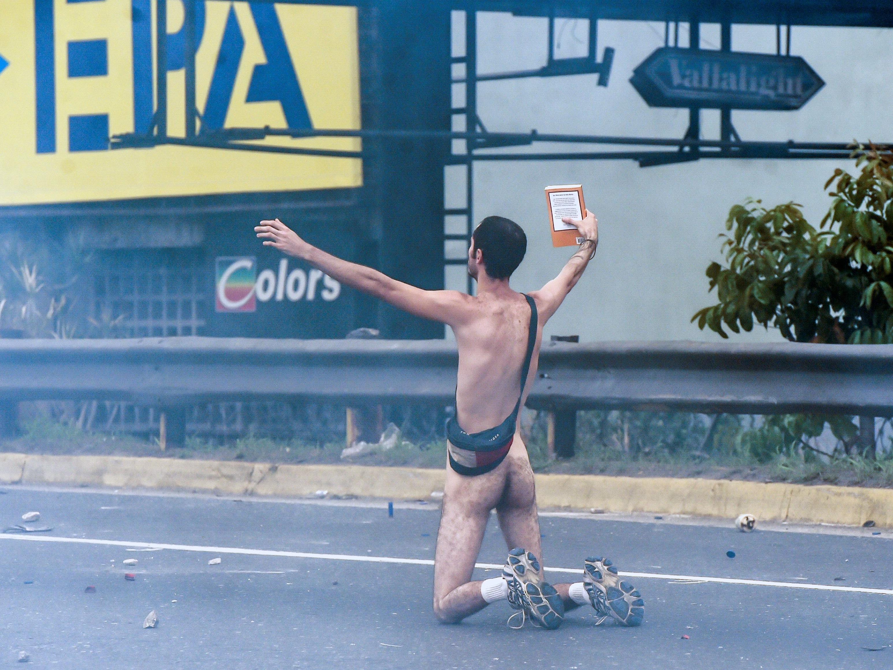 Mann stellt sich nackt vor einem Panzer.