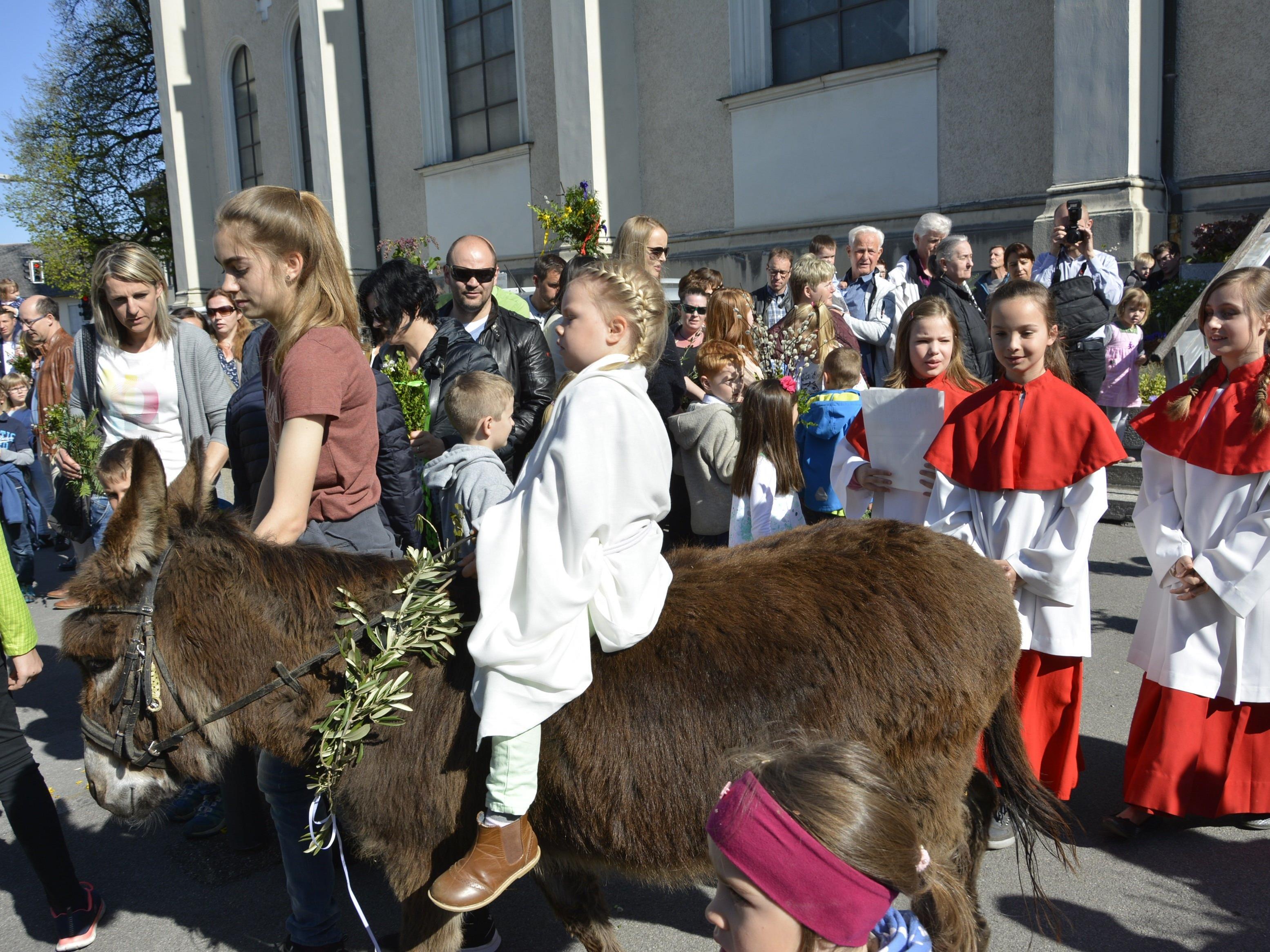 Anika saß auf dem Rücken der Eselin, die von Laura auf den Kirchplatz geführt wurde.