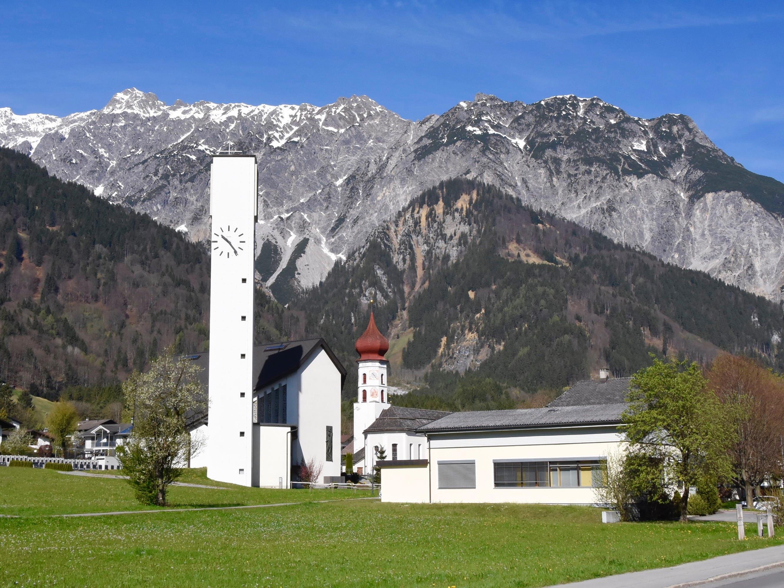 Neue und Alte Pfarrkirche Vandans mit der Vandanser Steinwand in einer Aufnahme vom Mittwoch vor Ostern 2017