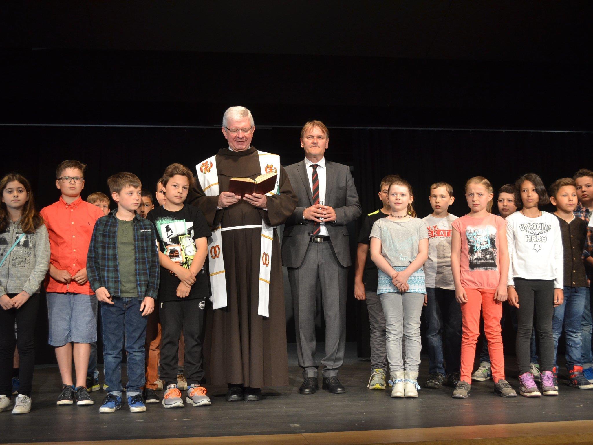 """Pater Adrian Buchtzik nahm mit dem Bürgermeister als """"Ministrant"""" sowie den Volksschulkindern die Segnung vor."""