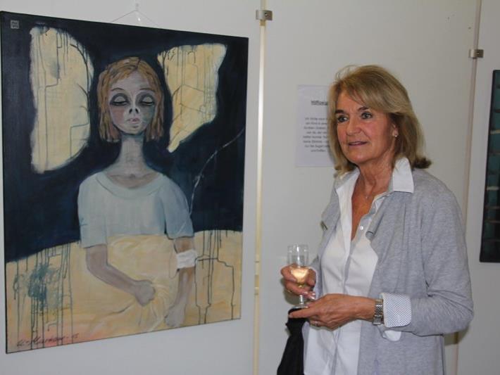 """Die Künstlerin """"U-Markow"""" vor einem ihrer Bilder bei der Vernissage im LKH in Feldkirch."""