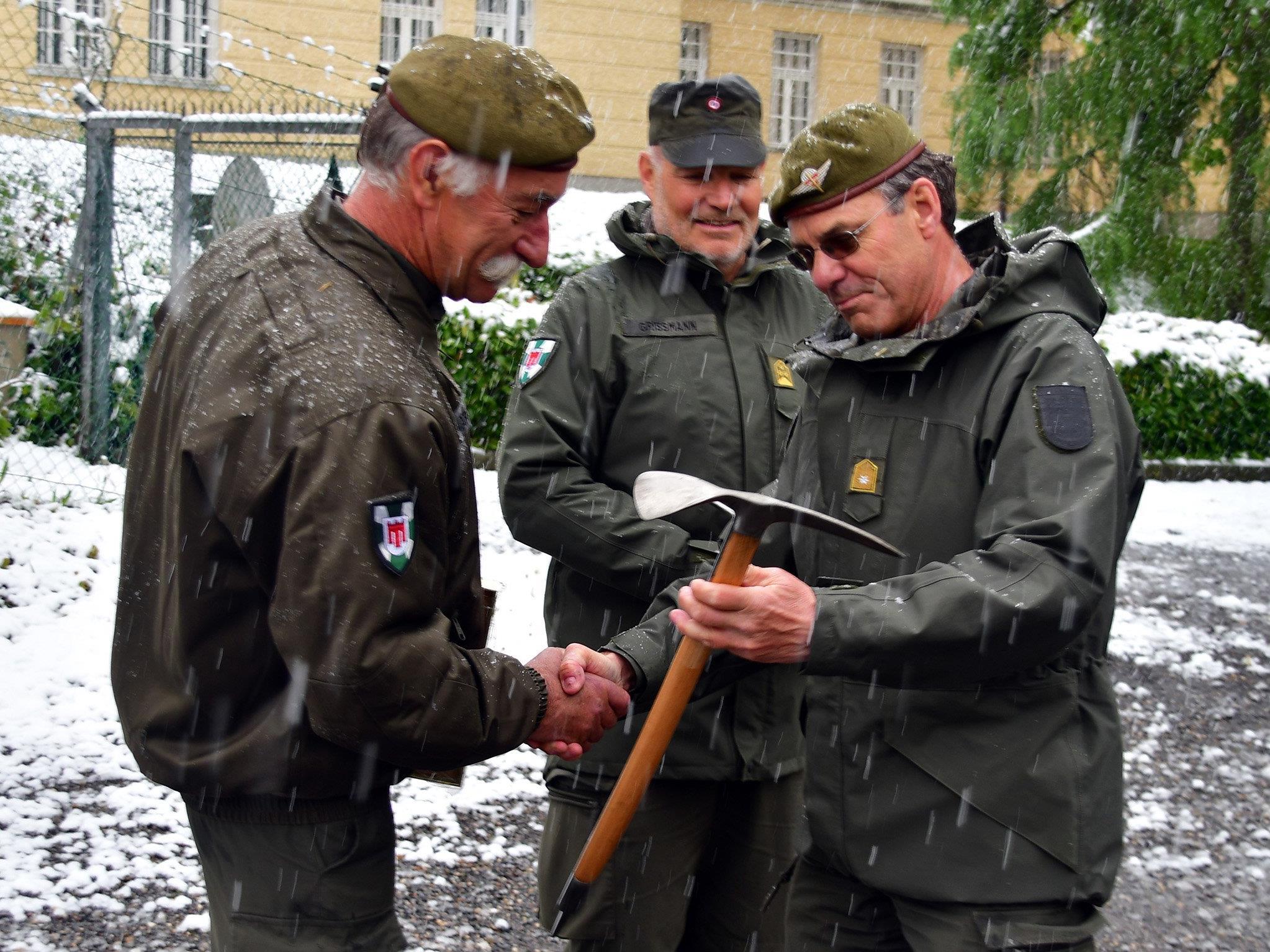 Brigadier Ernst Konzett (re.) überreicht Siegi Schwärzler (li.) und Johannes Grißmann symbolisch einen Eispickel.