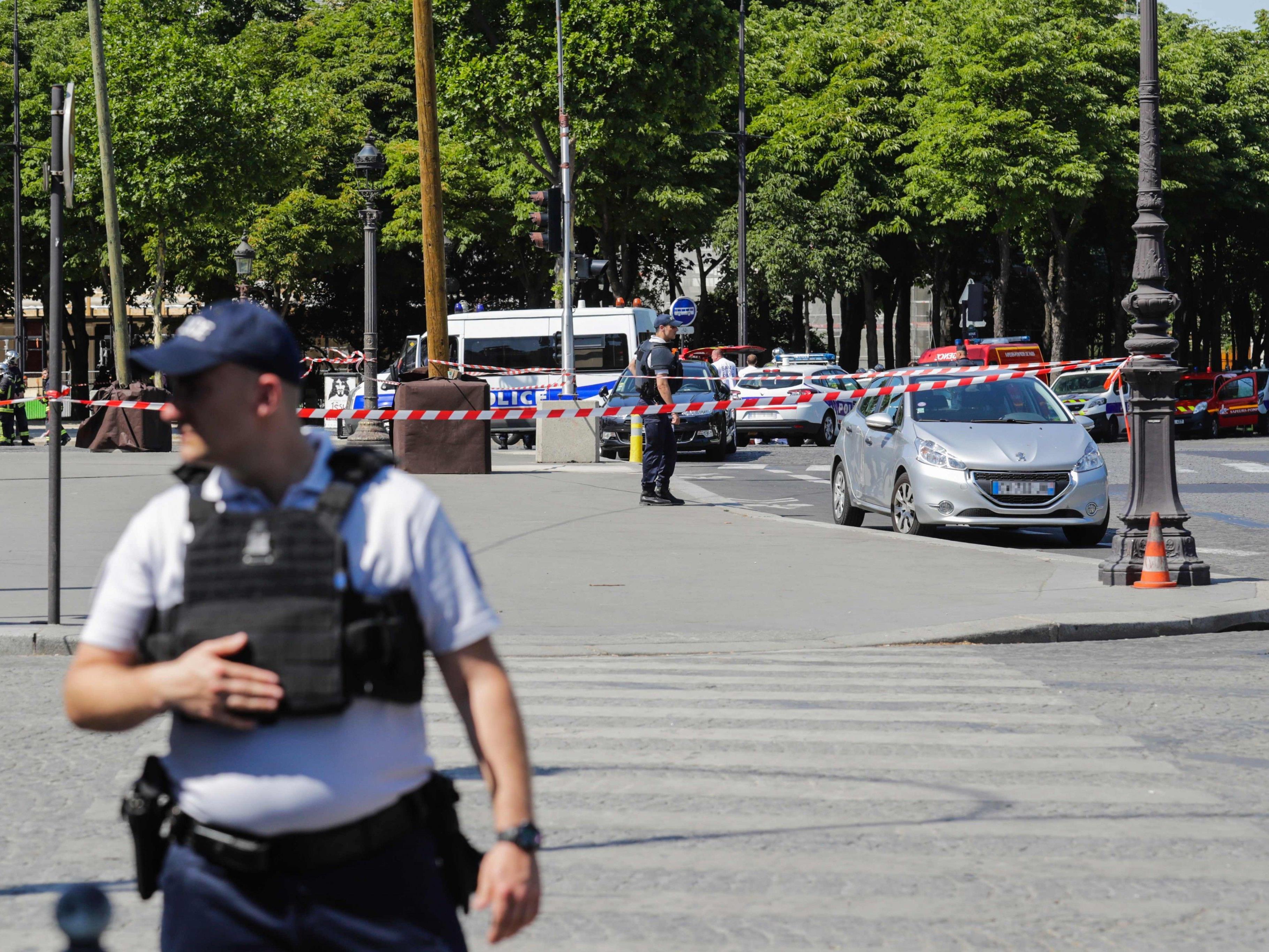 Auf der Pariser Champs-Elysees fuhr ein bewaffneter Mann in ein Polizeiauto.
