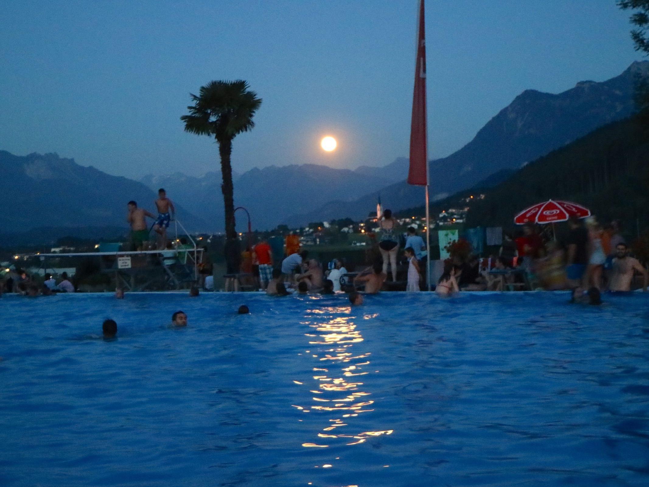 Der Panoramablick, wenn der Vollmond die Bergspitzen erleuchtet, ist ein ganz besonderes Erlebnis beim Vollmondschwimmen im ältesten Schwimmbad des Landes.