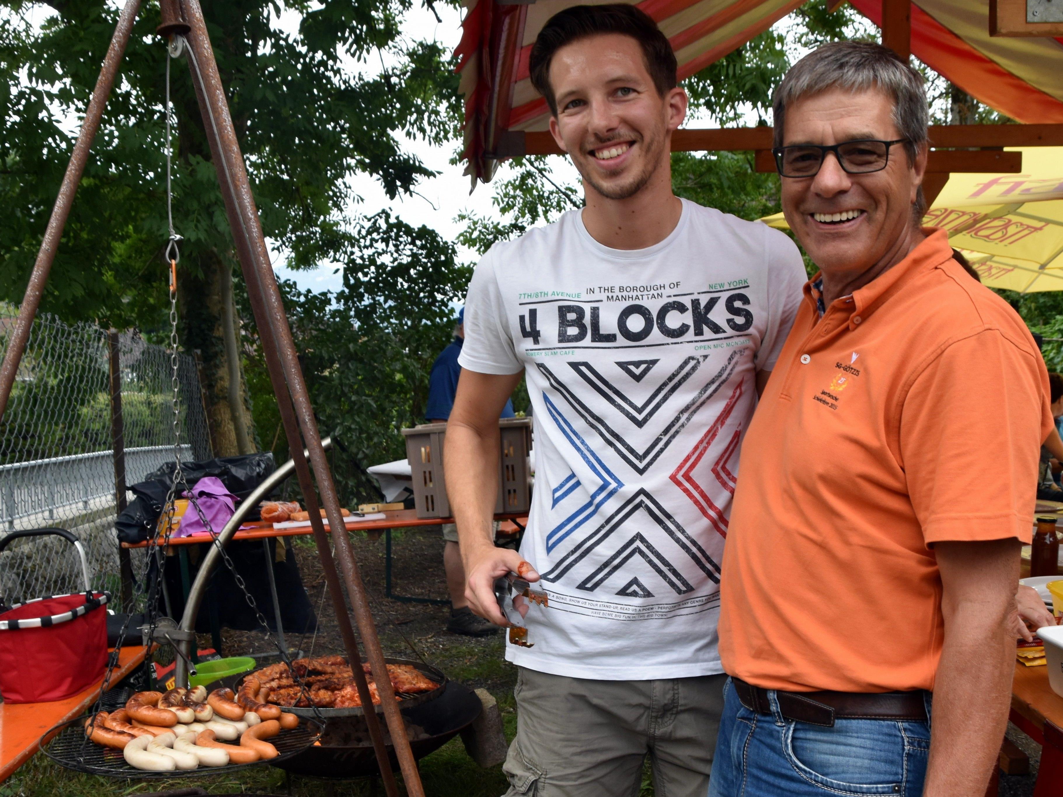 Philipp Frank und Organisator Michael Dünser grillen auf dem Holzkohlegrill für die Gäste
