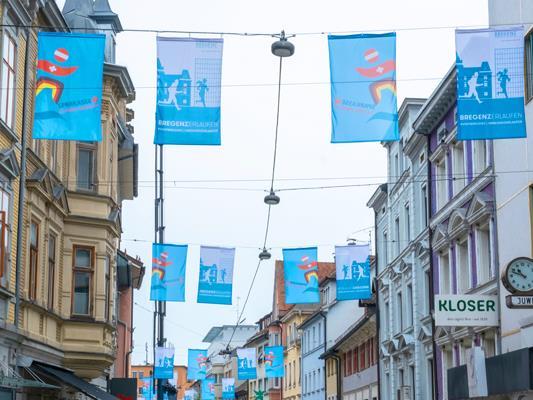 Auch mit eigenen Fahnen wie hier in der Bregenzer Fußgängerzone werden die großen Laufsportevents unterstützt.